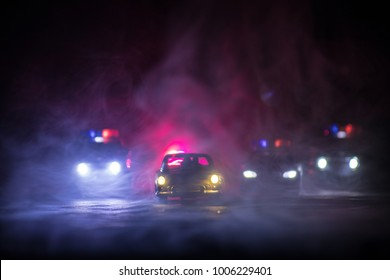 Toy BMW Police and Toyota FJ Cruiser cars chasing a Ford Thunderbird car at night with fog background. Toy decoration scene on table . Selective focus - 11 JAN 2018, BAKU AZERBAIJAN