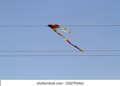 Toy bright flying kite tangled in the wires