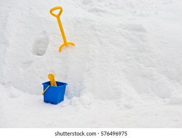 Toy bucket and spade with snow isolated on white background/ Winter/ Horizontal