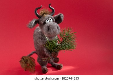 Toy bull. The bull is a symbol of the new year 2021. A knitted brown toy bull on a red background sits on its hind legs with a pine branch in its mouth. Copy space, close-up, selective focus.
