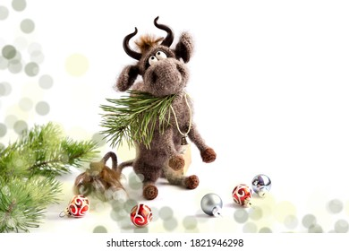 Toy bull. The bull is a symbol of the new year 2021. A knitted brown toy bull on a white background sits on its hind legs with a pine branch in its mouth. Copy space, selective focus.