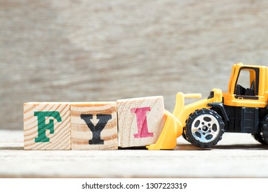 Toy bulldozer hold letter block I to complete word FYI (Abbreviation of For your information) on wood background