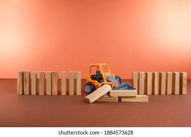 A toy bulldozer with pile of wooden sticks  on the brown background