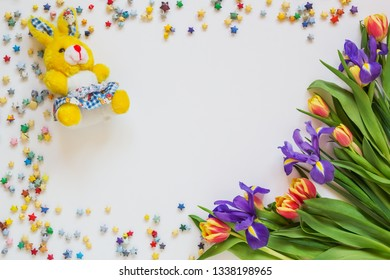 Toy bunny and a bouquet of flowers on a white background, blank