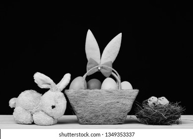 Toy bunny on yellow wooden table by Easter egg in nest. Bunny ears head band in pink color on black background. Easter symbols concept. Fluffy rabbit ears with colorful eggs in green cloth basket.