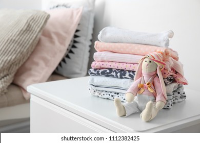 Toy bunny and stack of stylish child clothes on table indoors