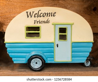 Toy camping trailer in blue and white with welcome friends painted on it.