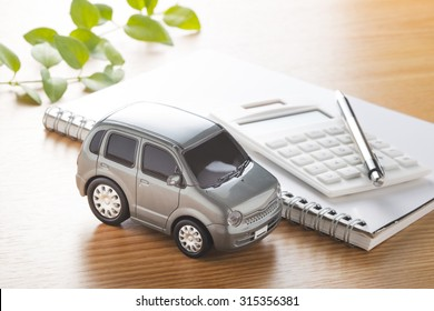 Toy car and calculator on the table.,to buy,sell,rent,repair or insurance
