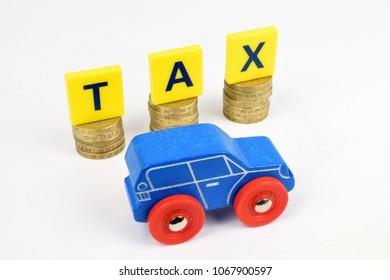 A toy car infront of stacked coins with the letters TAX. A still-life representing the cost of motoring.