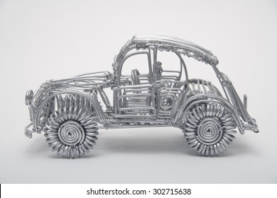 Toy car made of pliable wire against white background,close up