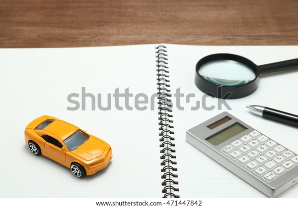 Toy car, magnifying glass, calculator, pen and notebook. Rent, buy or insurance car concept. +++NOTE TO INSPECTOR: THE ITEMS USED IN THIS IMAGE ARE GENERIC AND PURCHASED AT A DISCOUNT SHOP+++