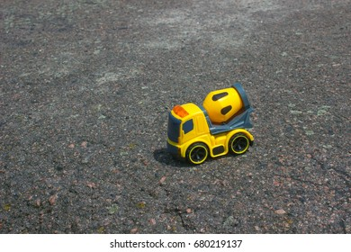 Toy car mixer on the dark asphalt