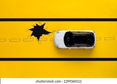 Toy car on drawn road with pothole. Safety concept. Yellow background.