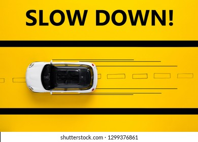 Toy car on drawn road demonstrates high speen. Safety concept. Yellow background