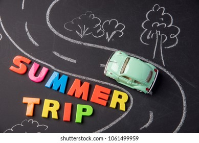 Toy car on the road chalked and inscription plastic letters summer trip on chalkboard