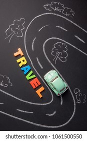 Toy car on the road chalked and inscription plastic letters travel on chalkboard