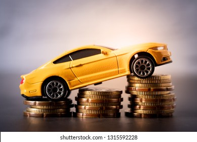 Toy car on stacked coins concept of increase in sales, insurance, price, maintenance cost etc.