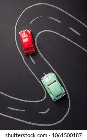 Toy car red and green color on the road chalked on black chalkboard