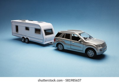 Toy car towing a caravan of generic design on blue background