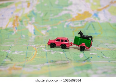 A toy car with a trailer to transport a horse. The pink car is traveling by geographic map. The concept of farming.