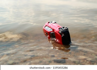toy car turned on its side in the water, a summer day at the pond on the beach