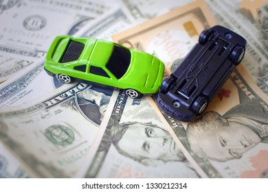 Toy cars in acciden on a background of 100 dollar bills