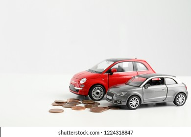 Toy cars and money on white background, space for text. Vehicle insurance