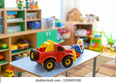 toy cars on the table.Children's playroom with plastic colorful educational blocks toys. Games floor for preschoolers kindergarten. interior children's room. Free space.