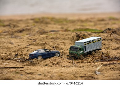 Toy cars in the sand on the beach