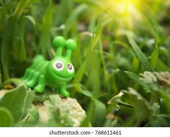 Toy caterpillar in grass. Conceptual scene.