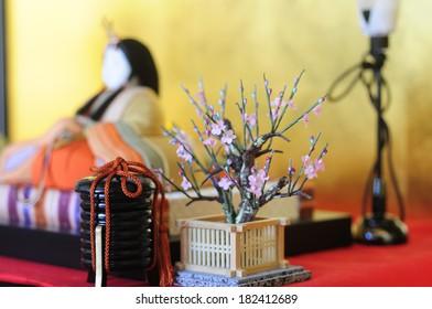 Toy cherry blossom tree next to hinamatsuri doll