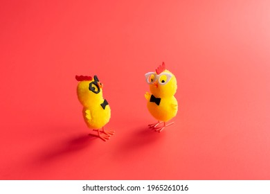Toy chickens on a red background, a parody of human relationships