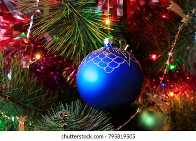 Toy Christmas blue ball on the Christmas tree background closeup