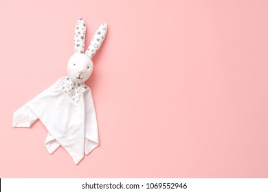 Toy Comforter bunny on a pink background. handy toy for grasping the hands of babies.