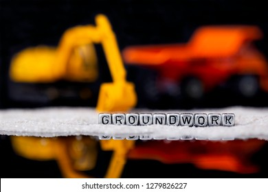 Toy construction vehicles and sand with the word groundwork on beads reflected on black background