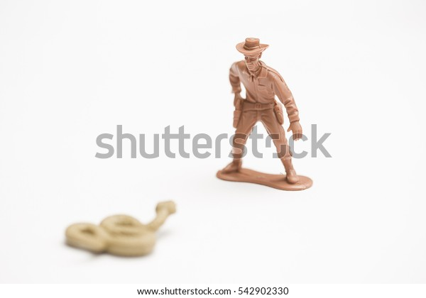 Toy cowboy threatened by a rattle snake