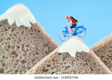 A toy cyclist is taking a ride on mountains, made of rye bread and creamy cheese. Ecotourism and healthy eating concept.