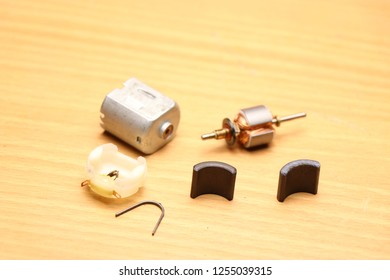 Toy dc motor which is disassembled so that parts can be studied here the parts are stator,rotor,magnets and pin