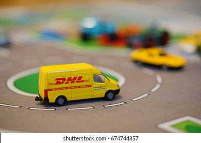 Toy DHL delivery bus on a roundabout of a playmat in soft focus on July 2017 in Poznan, Poland. Model is part of the Siku company collection.