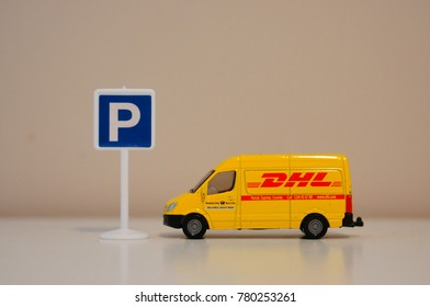 Toy DHL delivery bus parked by a parking sign in soft focus on December 2017 in Poznan, Poland