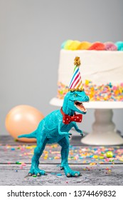 Toy dinosaur at a Birthday party wearing a hat and bow tie.