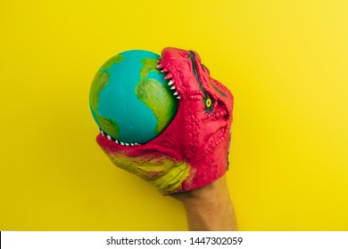 toy dinosaur nibbling   model of the Earth planet , concept of global cataclysm