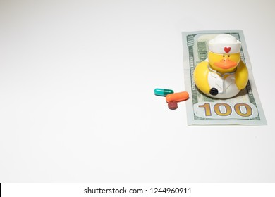 Toy duck dressed as nurse on one hundred dollar bill with prescrition pills