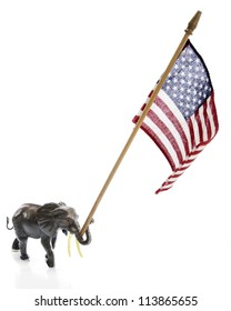 A toy elephant carrying a large (for him) American flag in its trunk.  On a white background.