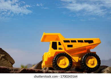 Toy excavator construction machine, clear blue sky