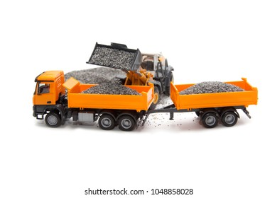 toy excavator loading of heavy dump-body track on white background