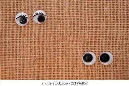 toy eyes on burlap background