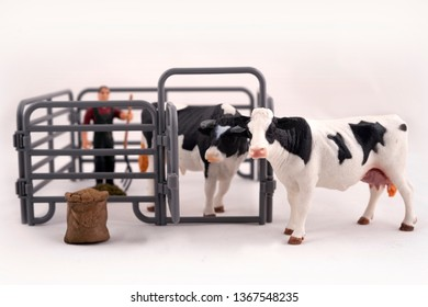Toy farm. Miniature plastic cows and a worker.