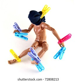 A toy figure being tortured with laundry clips
