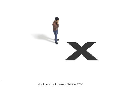 Toy Figure of a Man Standing Next to X Marks the Spot on a White Background